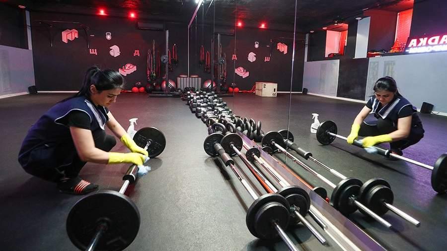 Работник фитнес-клуба во время дезинфекции спортивного инвентаря