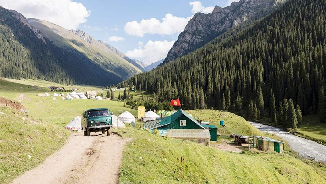 фургон едет через селение неподалеку от КАракола в Киргизии
