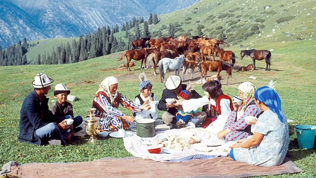 большая киргизская семья обедает на пастбище среди гор