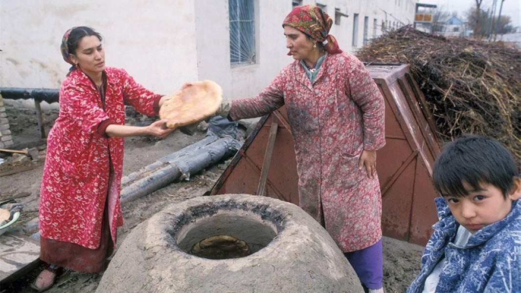 Женщины пекут лепешки втандыре на улице села Муграб