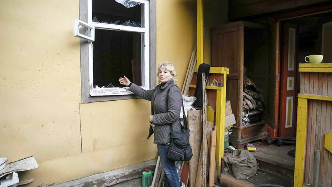 Местная жительница показывает окно