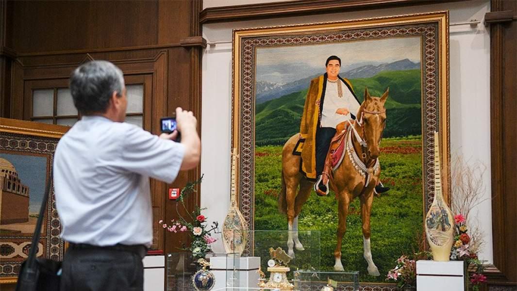 Мужчина фотографирует конный портрет президента Туркмении Гурбангулы Бердымухаммедова