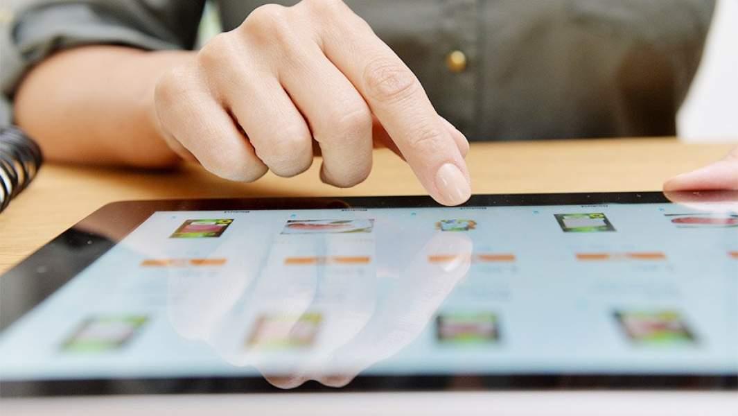 Женщина выбирает товар в интернет-магазине на планшете