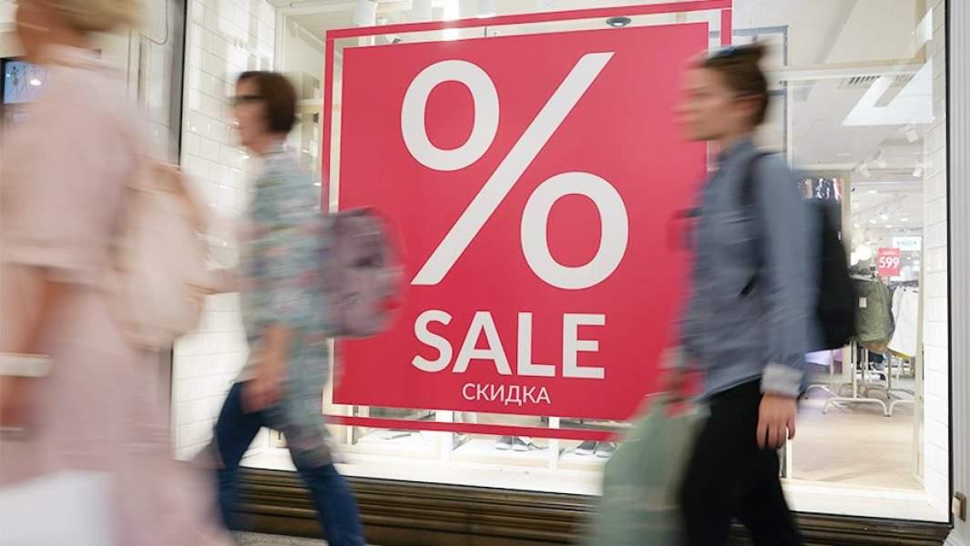 Люди проходят витрины с ообщением о скидках в магазине
