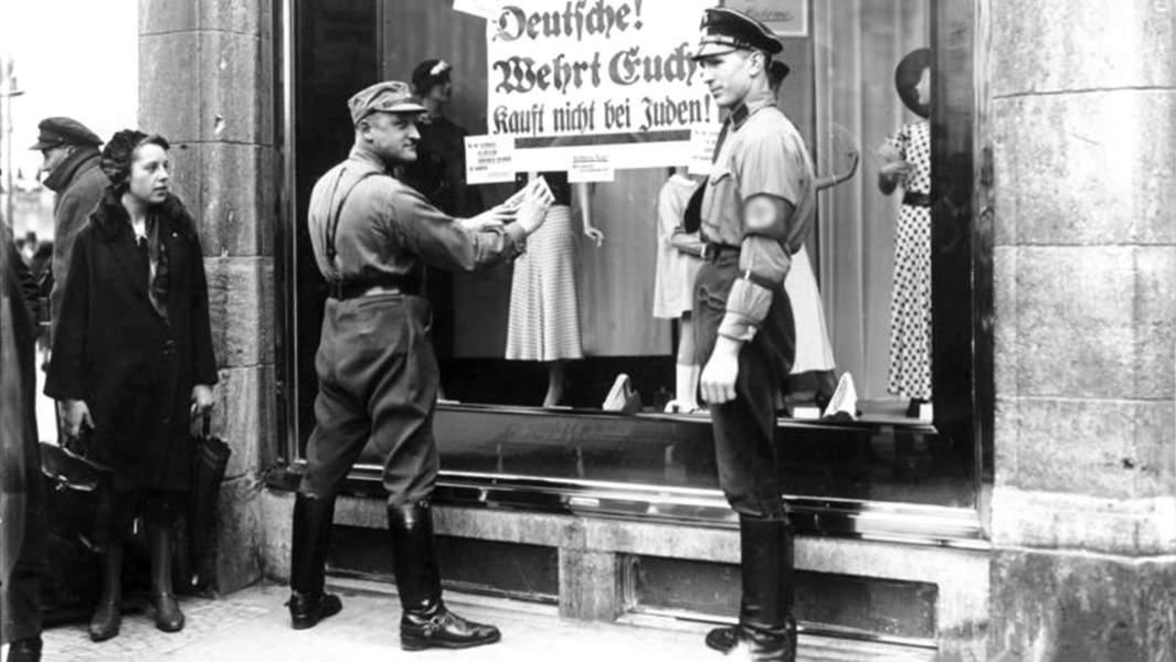 Штурмовики НСДАП вешают плакат, призывающий к бойкоту еврейские магазины