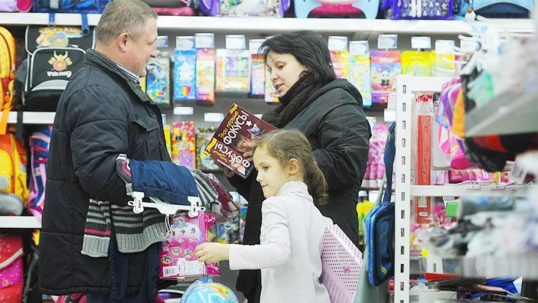 Родители с девочкой выбирают товары для школы