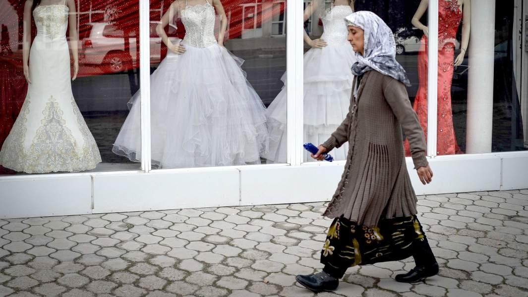 Женщина идет мимо салона для новобрачных в городе Душанбе в Таджикистане
