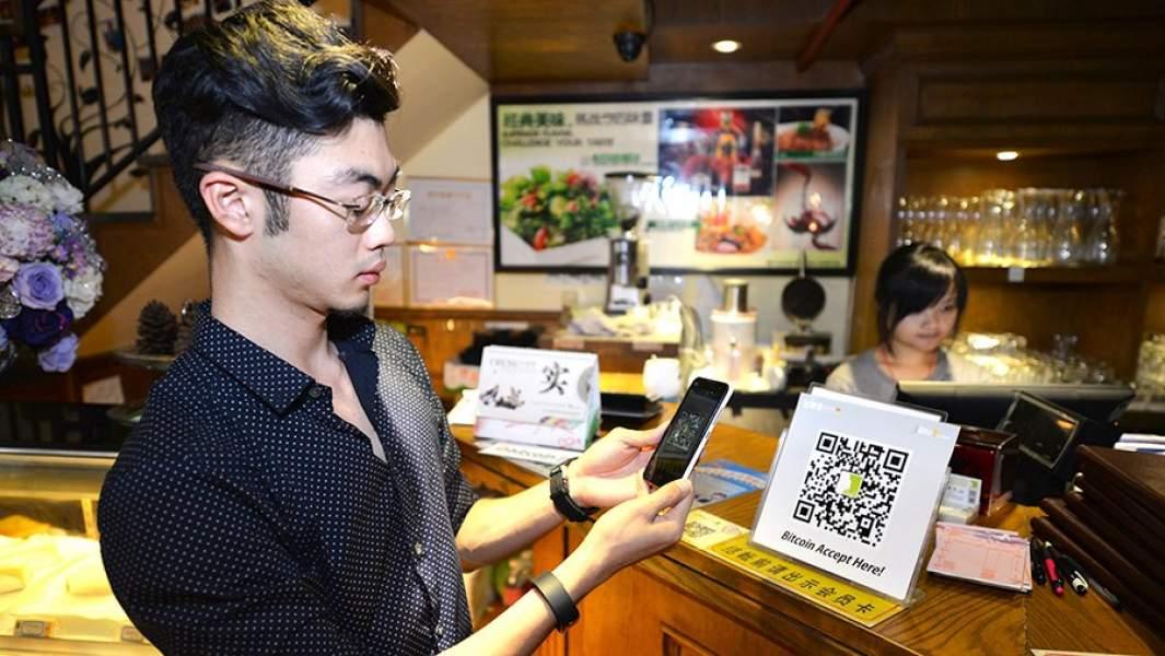 Клиент расплачивается биткоинами в кафе через приложение по QR-коду
