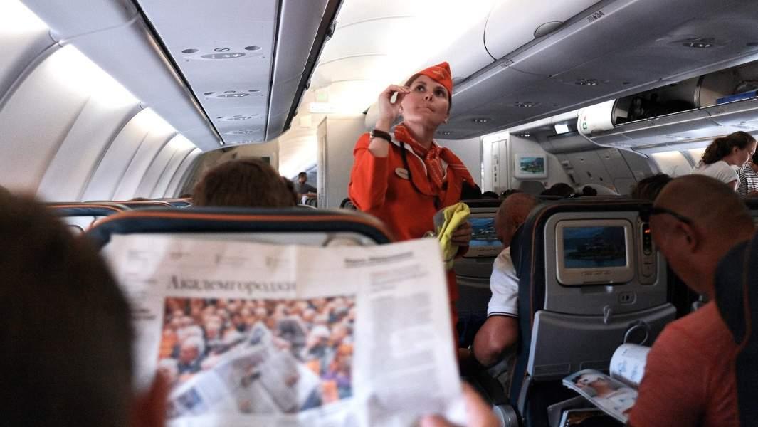 Пассажиры и бортпроводница в самолетево время полета