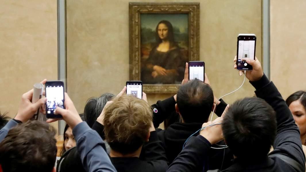 Посетители фотографируют картину «Мона Лиза» Леонардо да Винчи. Лувр,Париж