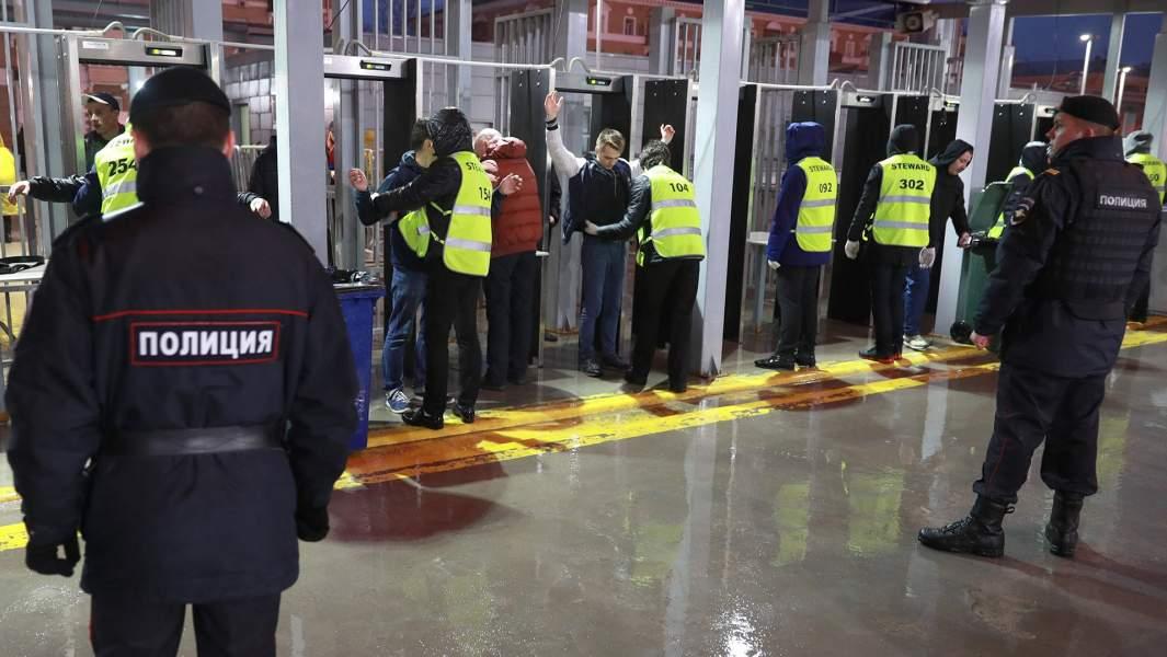 Сотрудники службы безопасности стадиона досматривают болельщиков перед началом матча