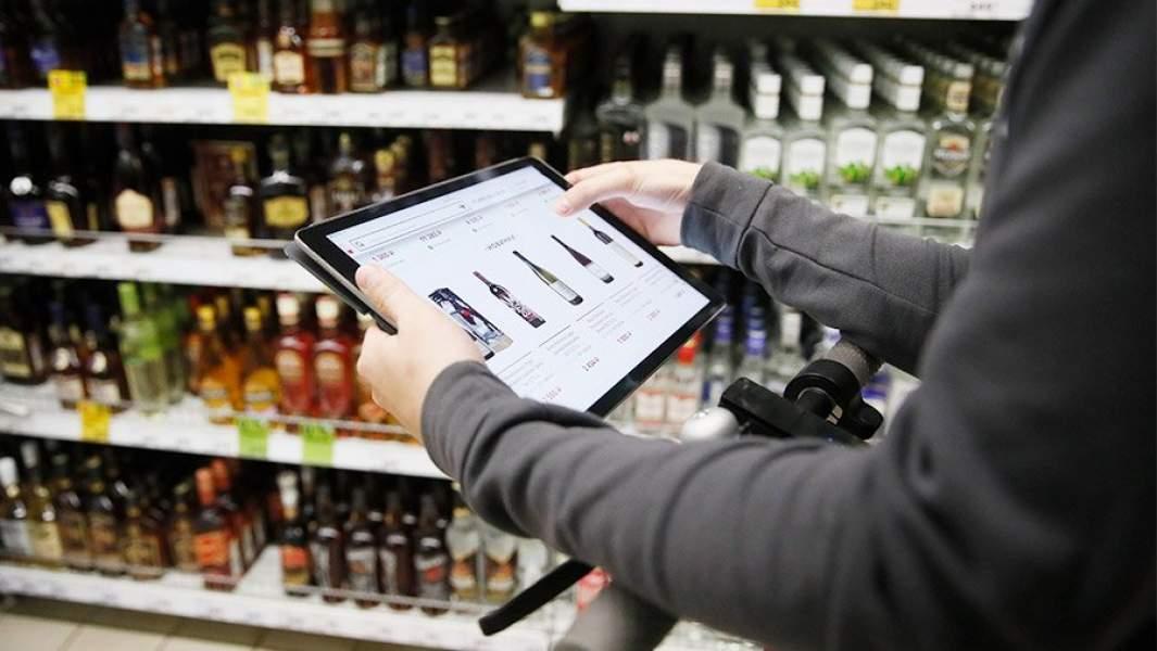 Человек выбирает вино в интернет-магазине, находясь в алкогольном отделе супермаркета