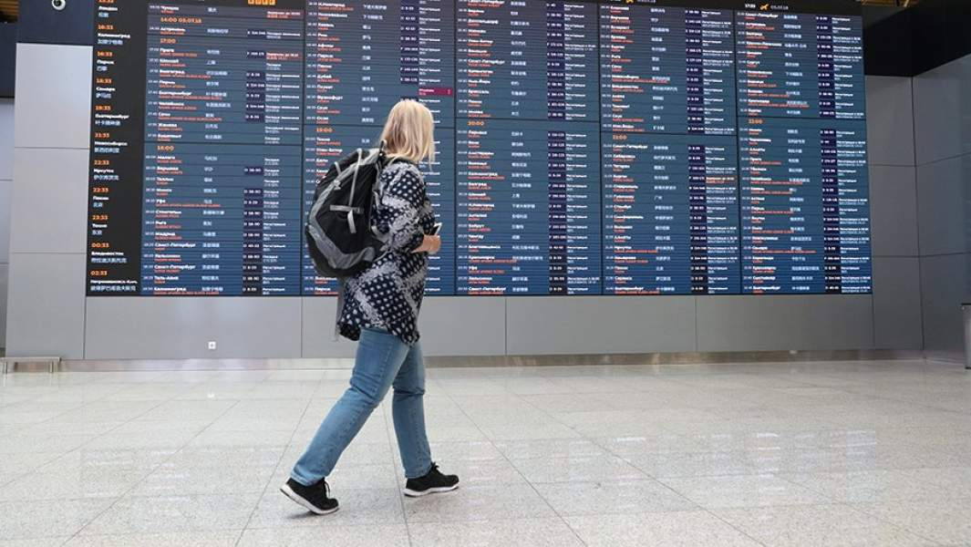 Пассажирка у табло расписания в аэропорту