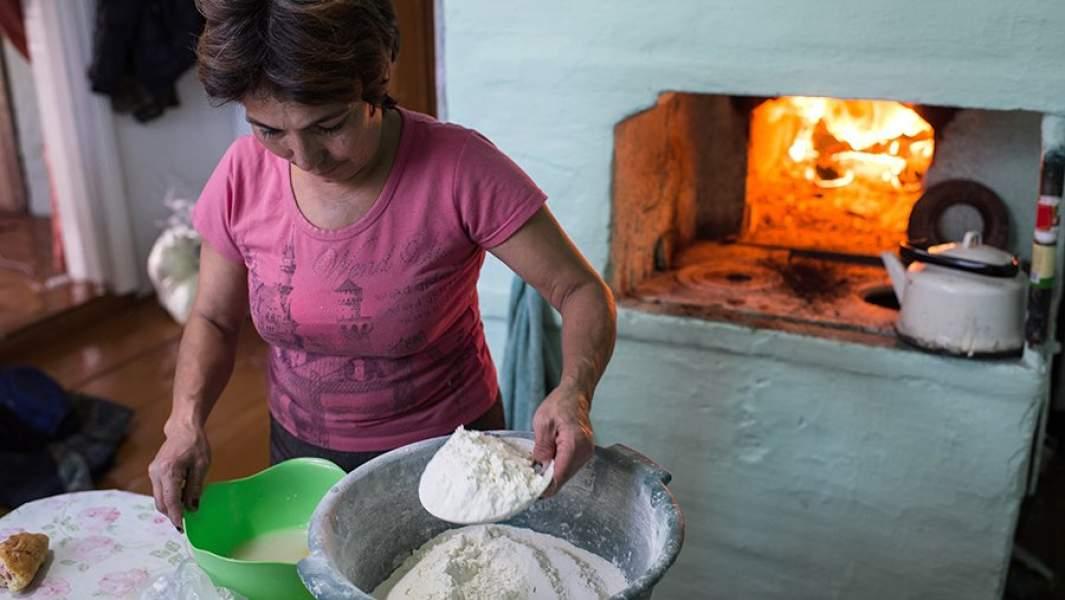 Жительница деревни Сибиляково Омской области готовит обед на печи