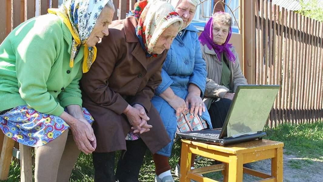 Пенсионерки смотрят телепередачу на ноутбуке во дворе сельского дома в Ивановской области