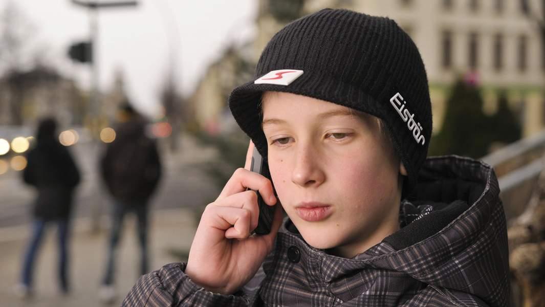 Подросток звонит по мобильному телефону