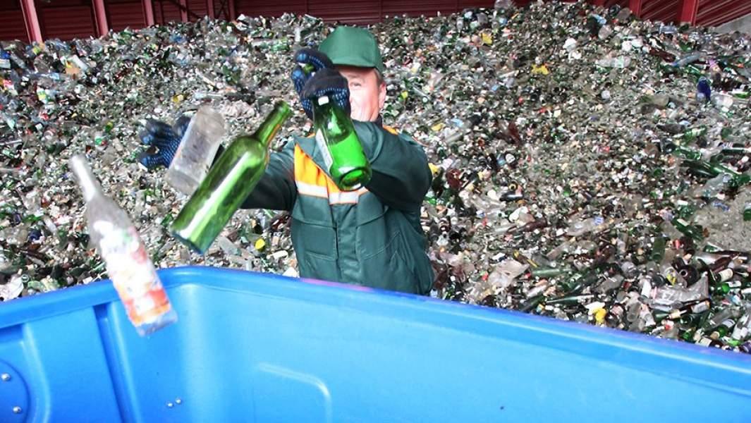 Рабочий наполняет контейнер на предприятии по сортировке и переработке смешанного тарного стеклобоя