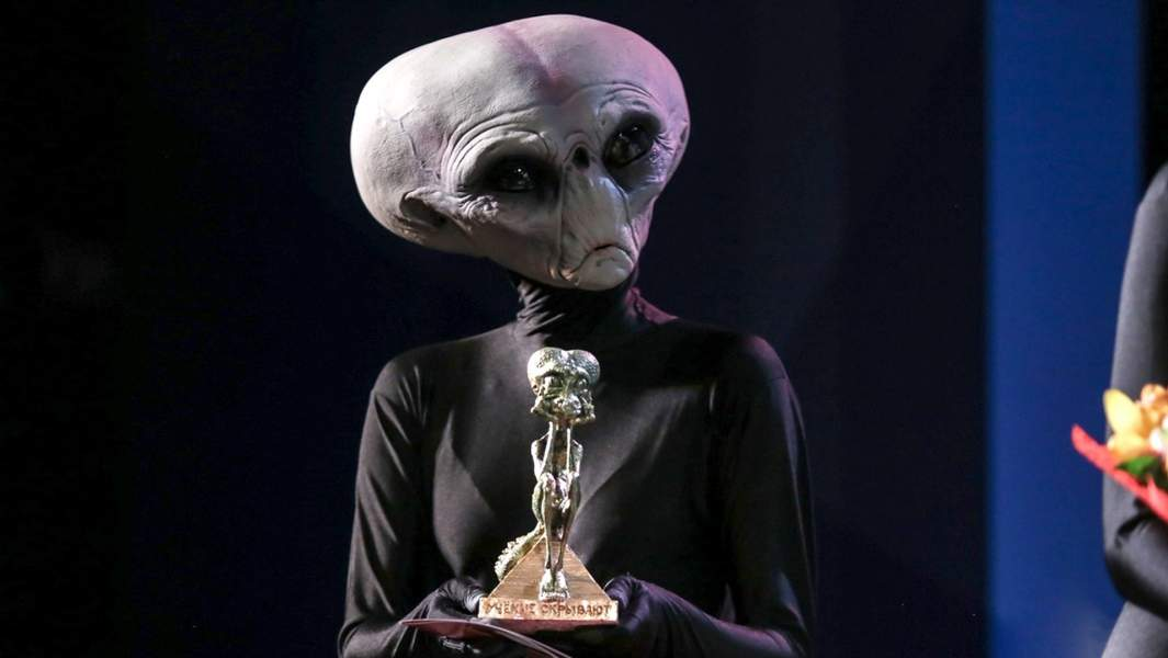 Пришелец со статуэткой «Грустный рептилоид» на вручении антипремии «Почётный академик ВРАЛ» в рамках научно-просветительского форума «Учёные против мифов-8»