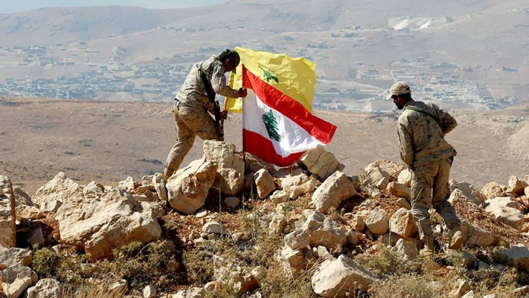 Бойцы ливанского движения «Хезболлах» устанавливают флаги на ливано-сирийской границе
