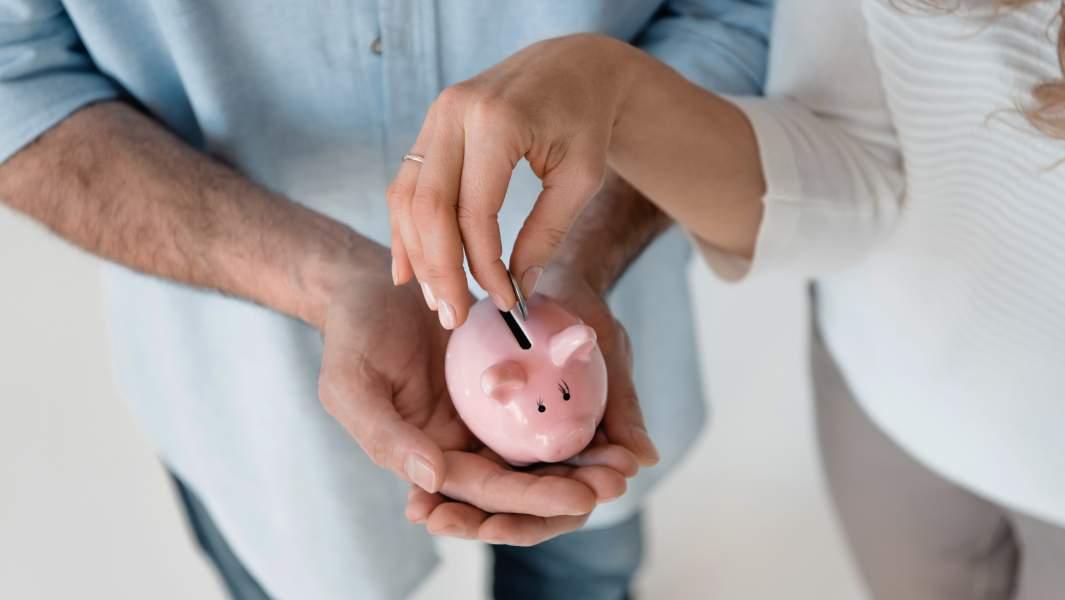пара кидают монеты в копилку-свинку