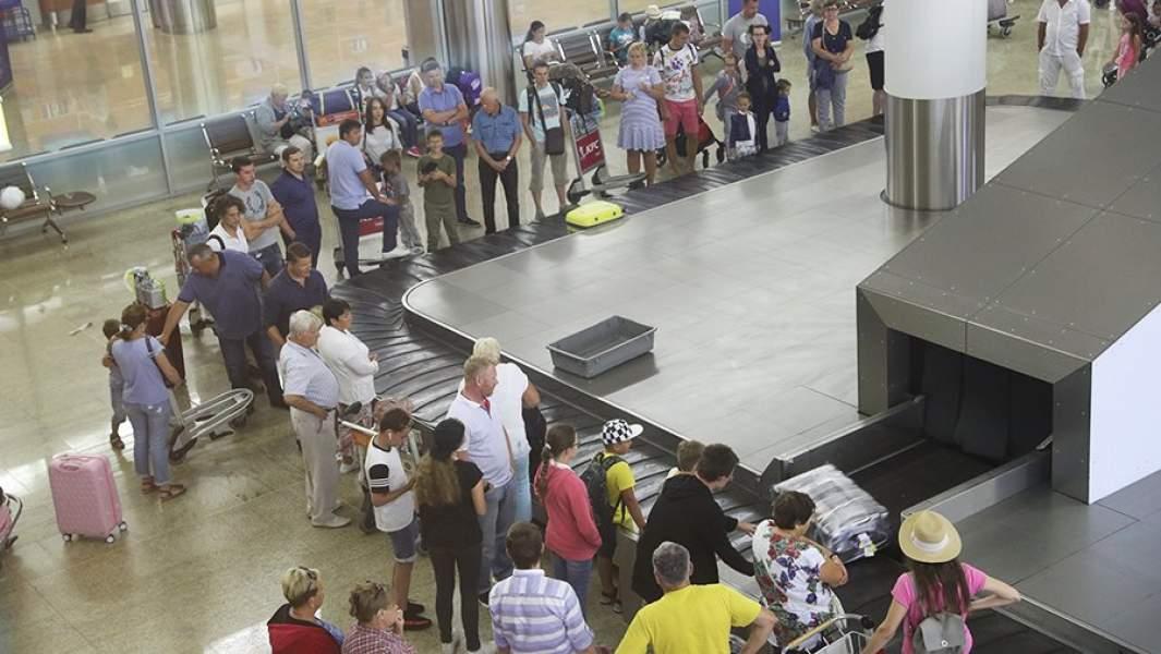 люди ожидают свой багаж в аэропорту