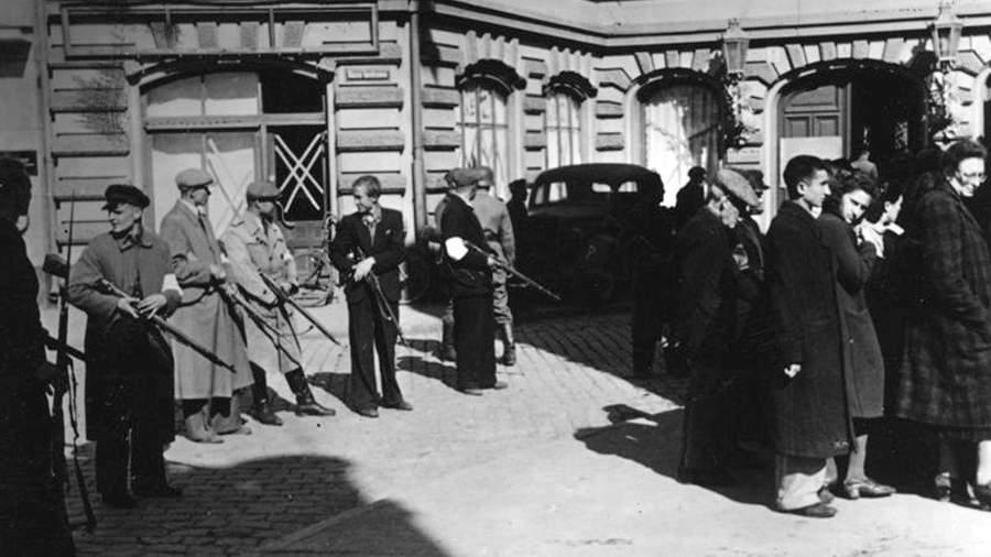 Члены Латвийской вспомогательной полиции конвоируют группу евреев. 1941 год