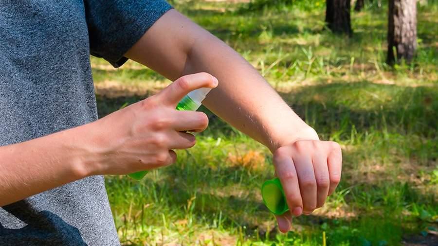 Девушка наносит спрей от комаров