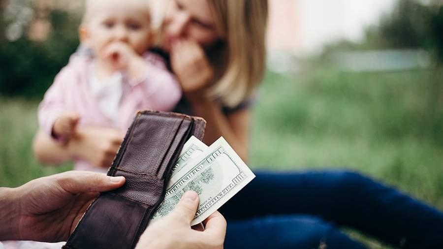 Мужчина достает из бумажника стодолларовые купюры для матери и ребенка