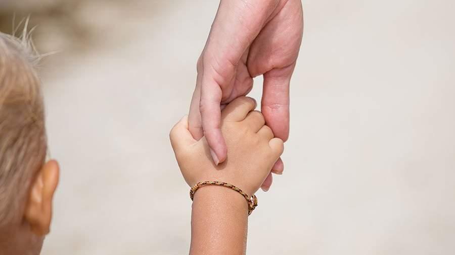 взрослый держит руку ребенка