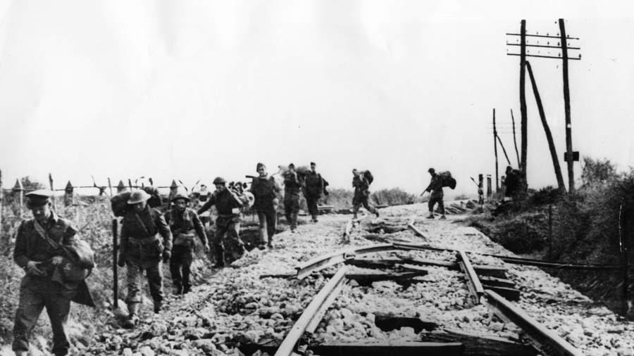 Британские солдаты идут вдоль разрушенной фашистами железной дороги в Италии