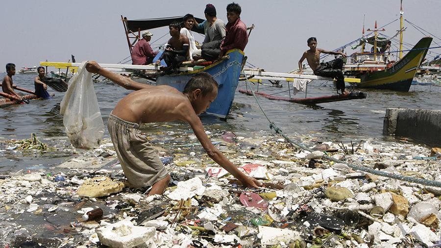 Мальчик собирает пластиковый мусор на побережье Филиппин
