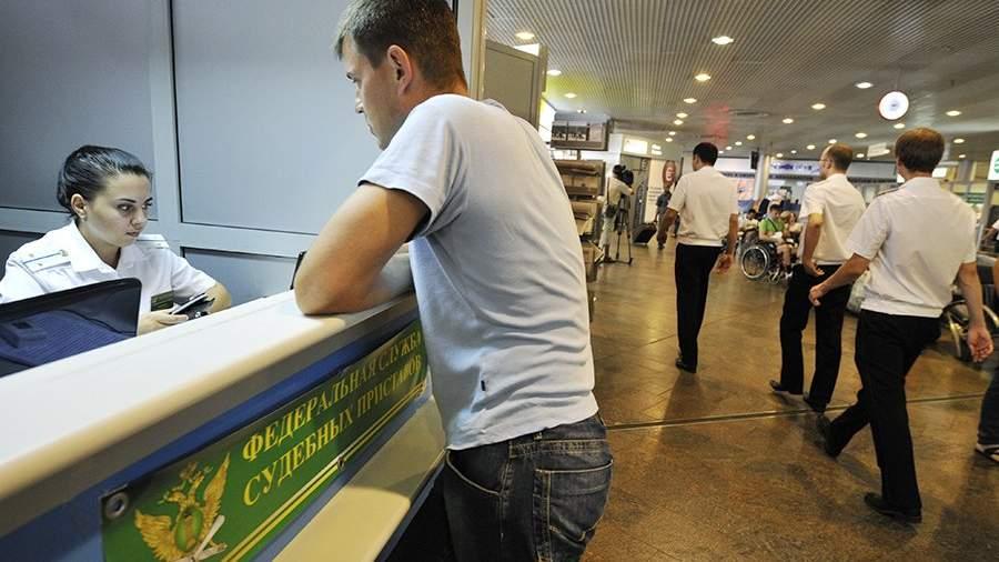 Пассажир у мобильного пункта Федеральной службы судебных приставов в терминале F международного аэропорта «Шереметьево»