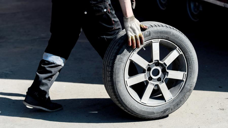 Работник меняет колесо в шиномонтажной мастерской