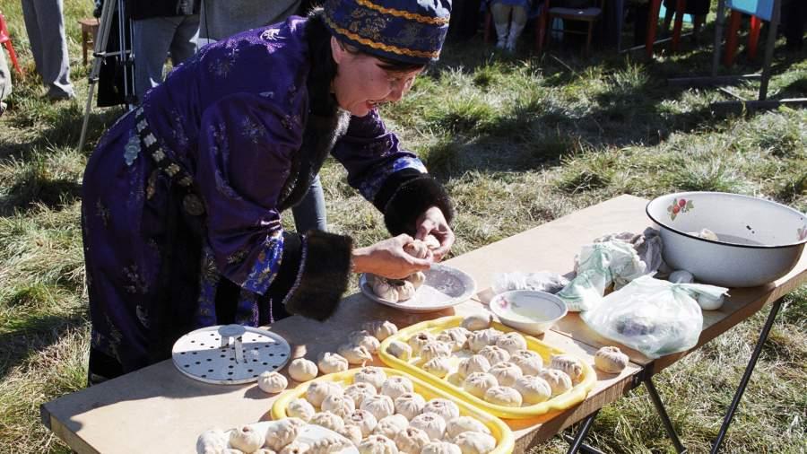 Женщина-бурятка готовит национальное блюдо бууза из баранины и муки на пару