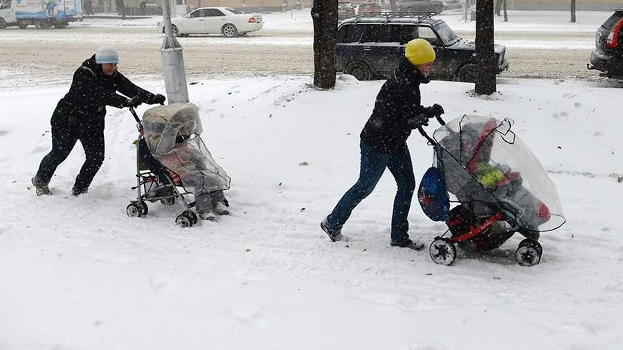 Женщины гуляют с колясками во время снегопада