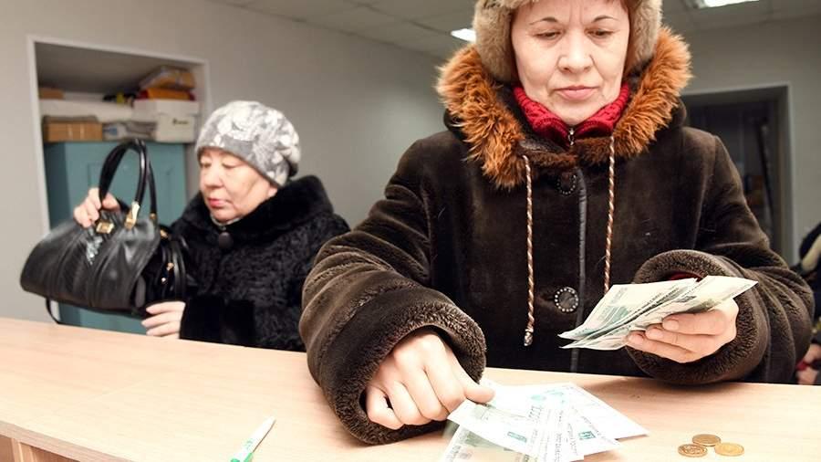 Женщина пересчитывает полученную пенсию на почтамте