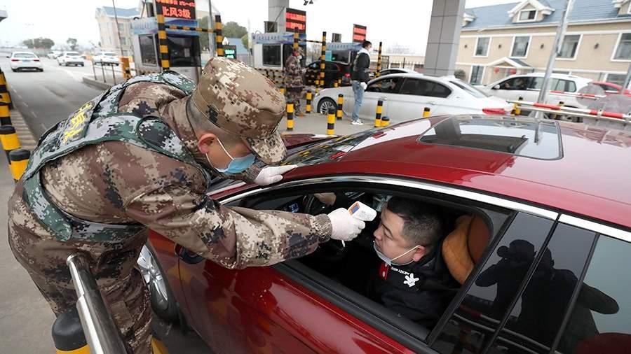 Сотрудник полиции проверяет температуру у водителя на одном из пропускных пунктов в Ухане