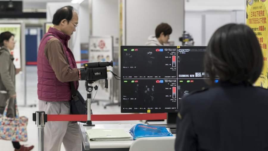 Медицинский работникпроверяет пассажиров аэропорта