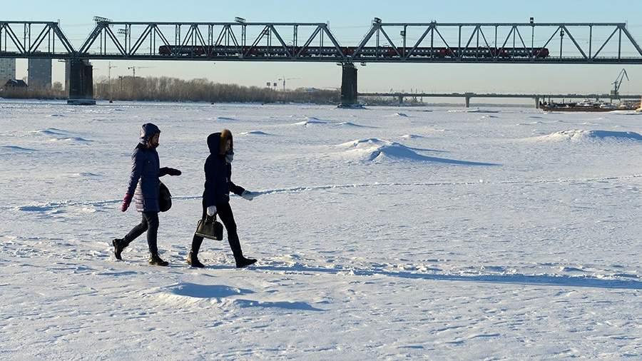 Горожане гуляют по замерзшей реке Обь у железнодорожного моста в Новосибирске