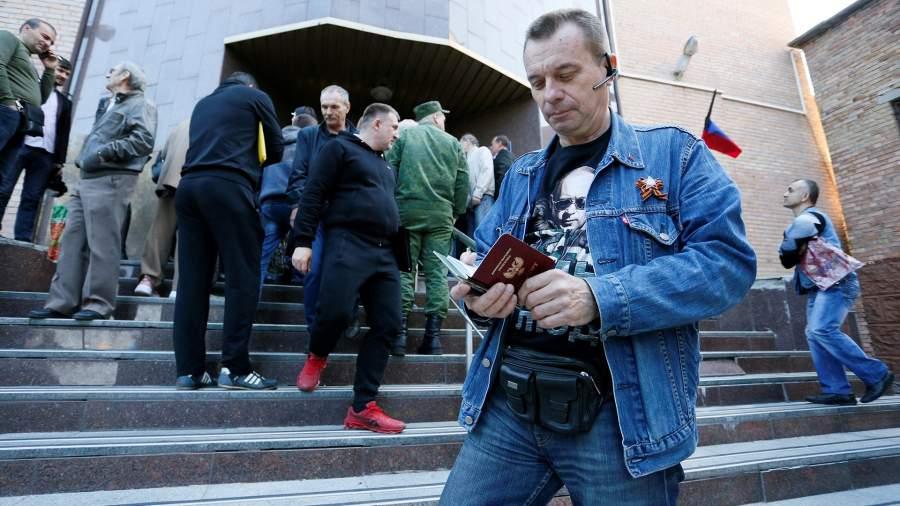 Мужчина держит паспорт у здания миграционной службы в Донецке