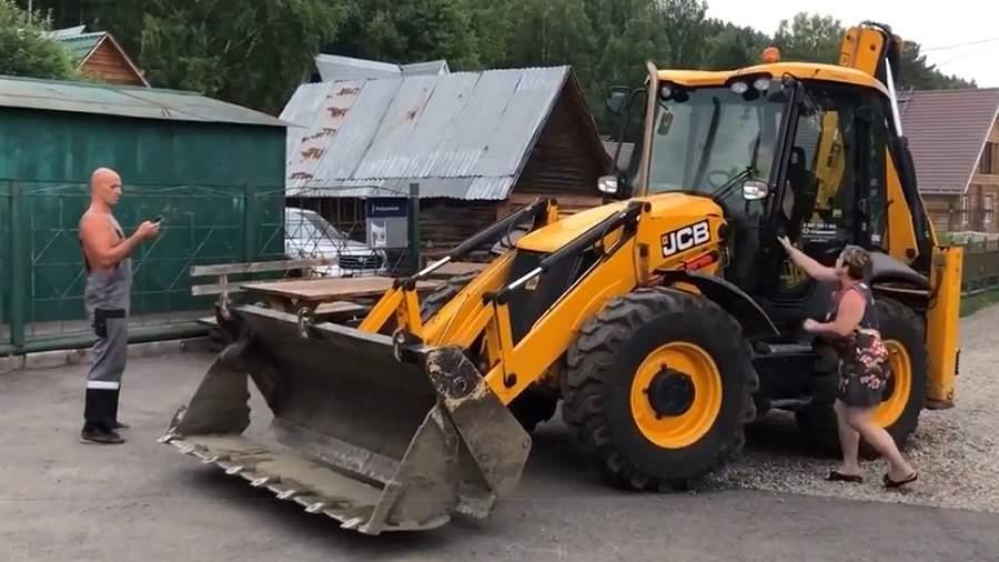 Стоп-кадр с видео, гдеСергей Чапайкин на тракторе пытается задавитьАртема Пакалова, а затем таранит его гараж