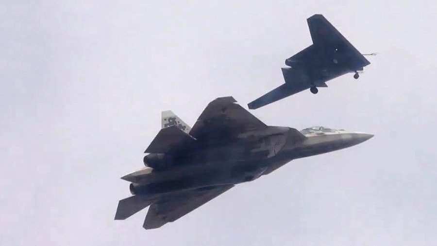 Ударный беспилотник «Охотник» (на втором плане) во время первого совместного полета с Су-57 на одном из испытательных аэродромов Минобороны России