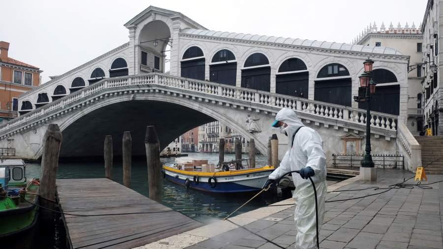 Рабочий дезинфицирует мост Риальто в качестве меры против коронавирусной болезни в Венеции, Италия