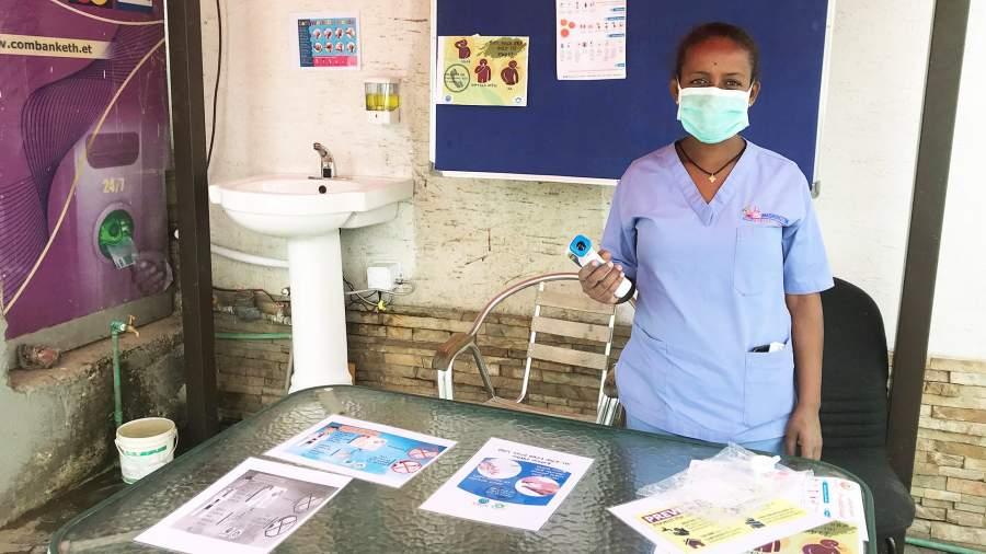 Медсестра у информационной стойки, посвященной коронавирусу,