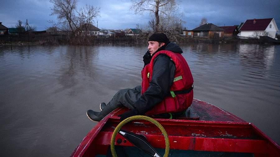Спасатель на лодке во время работ в затопленной части одного из городовАлтайского края