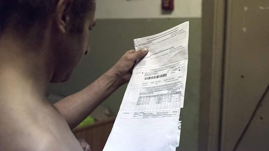 Мужчина держит квитанцию оплаты коммунальных услуг в подъезде жилого дома