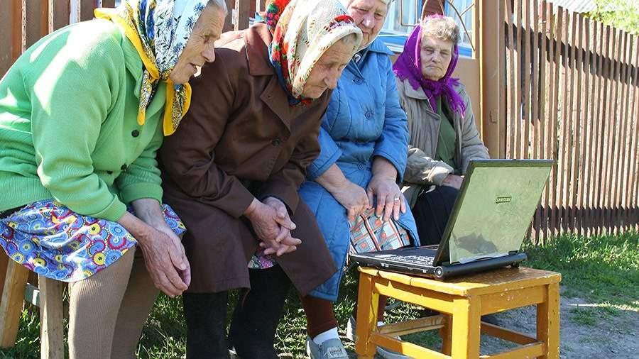Пенсионерки рассматривают ноутбук во дворе сельского дома