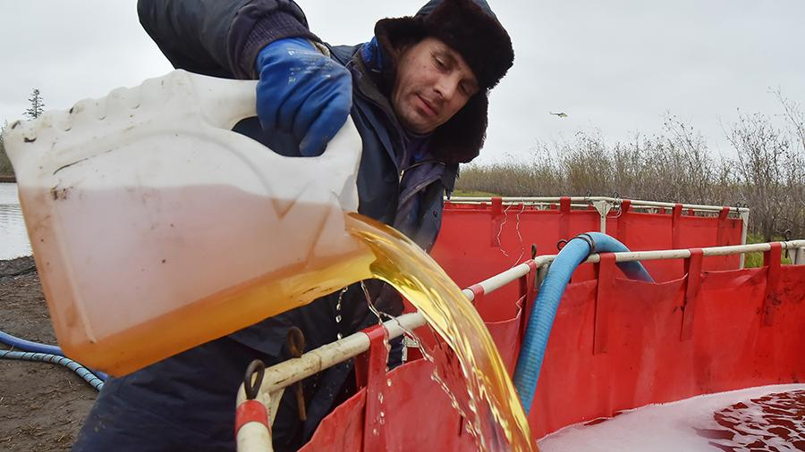 Сотрудник специальной службы наполняет временный резервуар топливом, собранным из реки Амбарной