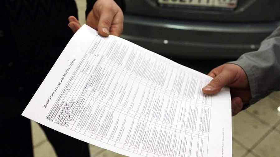 Сотрудник сервисного центра передает диагностическую карту владельцу транспортного средства