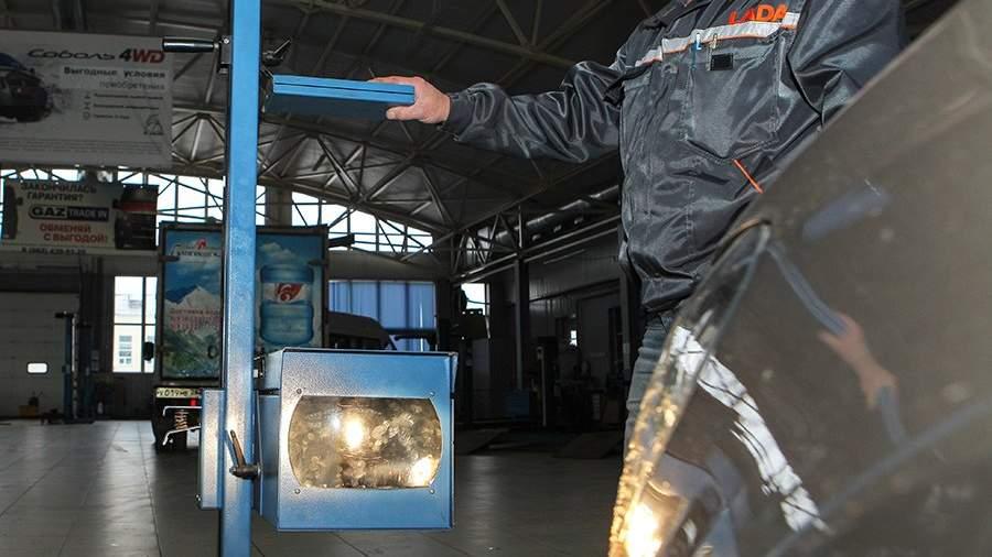 Сотрудник станции проводит технический осмотр автомобиля